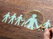 High Angle View Of Person Hand Using Magnifying Glass On Cut-out Figures On Wooden Desk